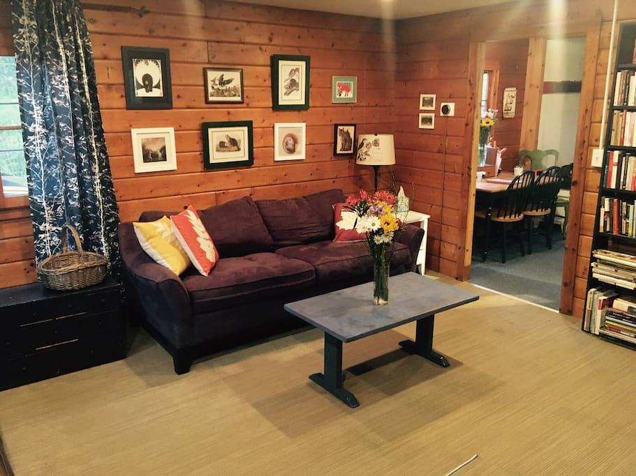 The cozy living room has knotty pine walls all around, a wood burning stove that keeps the whole house toasty in the winter, two comfy couches (the one pictured folds out into a queen bed) and art featuring local animals.