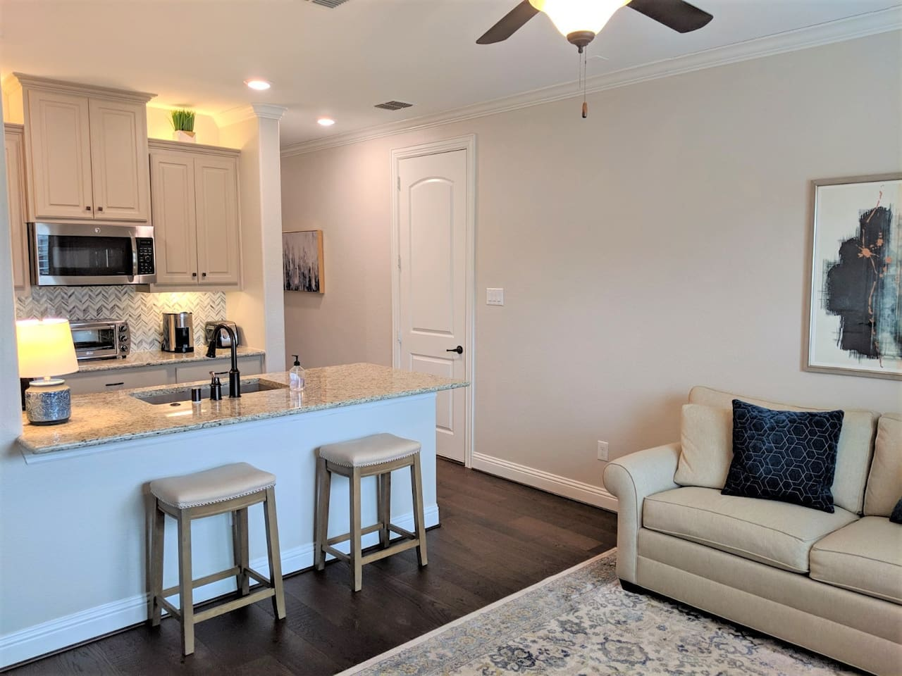 The guest suite  has an open floor plan with sitting area adjacent to kitchen and beautiful hardwood floors.