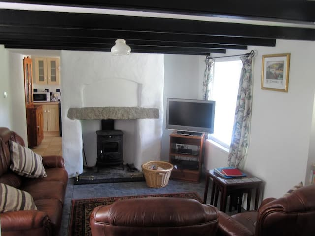 Lounge with woodburner in fireplace, TV DVD player, playstation, central heating, view of tree lined valley.