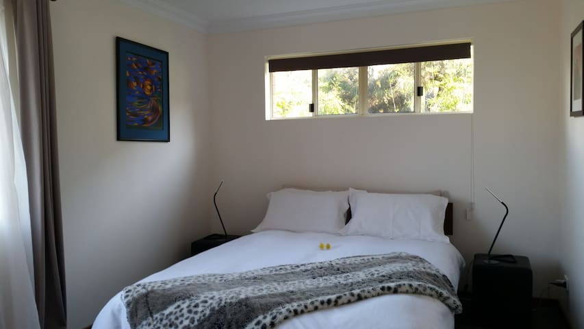The main bedroom has a super comfy queen bed with garden outlook and ocean aspects. Block out curtains and built-in wardrobe.  Plenty of pillows and extra blankets.