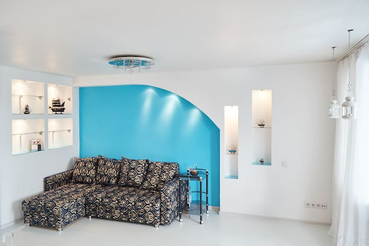 Perception of space in the living room is reached due to the absence of furniture, as it is comfortably built in the walls and has its own lighting.
