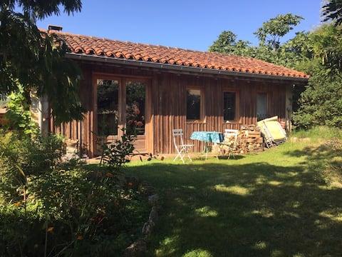 Petite maison bois et pierre dans un jardin fleuri