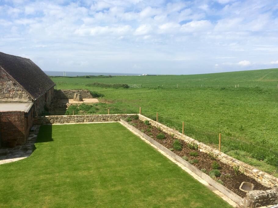 Enclosed south facing rear garden bordered by open fields overlooking the sea.
