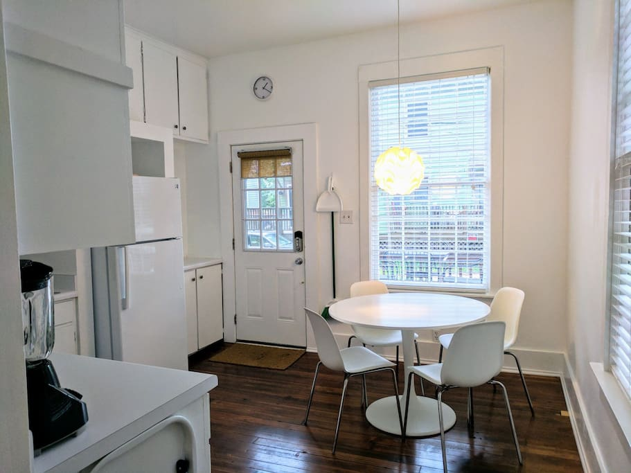 The kitchen viewed from the living room. A large cafe table and chairs serve as the main dining area. The kitchen also features two large wooden windows and is accessible to the back door, which is where guests will enter upon arriving.
