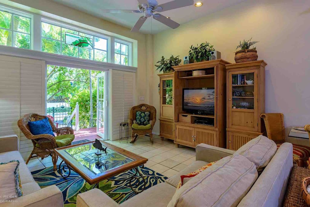 The living room has plenty of comfortable seating and a flat screen TV...