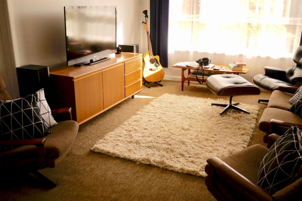 A touch of Mid Century Modern. Old school timber swivel chairs, sofa & luxurious Eames lounge chair. Surround sound Home Theatre with Blu-Ray, Apple TV & unlimited Netflix.  Acoustic Guitar for strumming tunes when the urge strikes