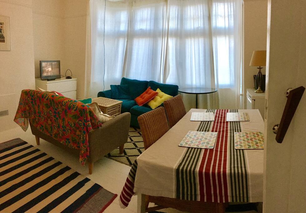 Tv room with two sofas and cushions. Internet cable. Second fridge for cakes and drinks.  Dining table and four chairs. Bookcase with books and toys.
