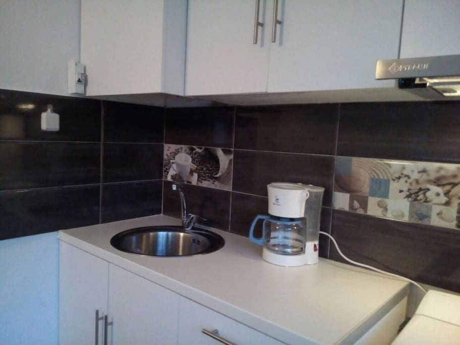 Small but fully equipped kitchen includes an oven and a cooking panel, microwave, washing machine, coffeemaker and a fridge.