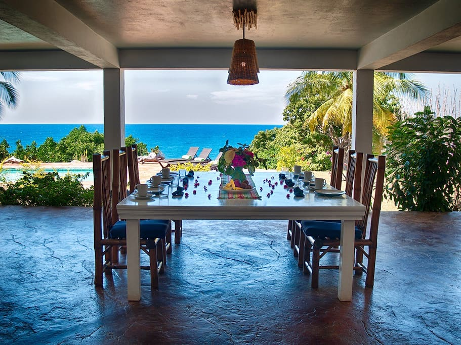 Veranda with large dining table and view of the sea.
