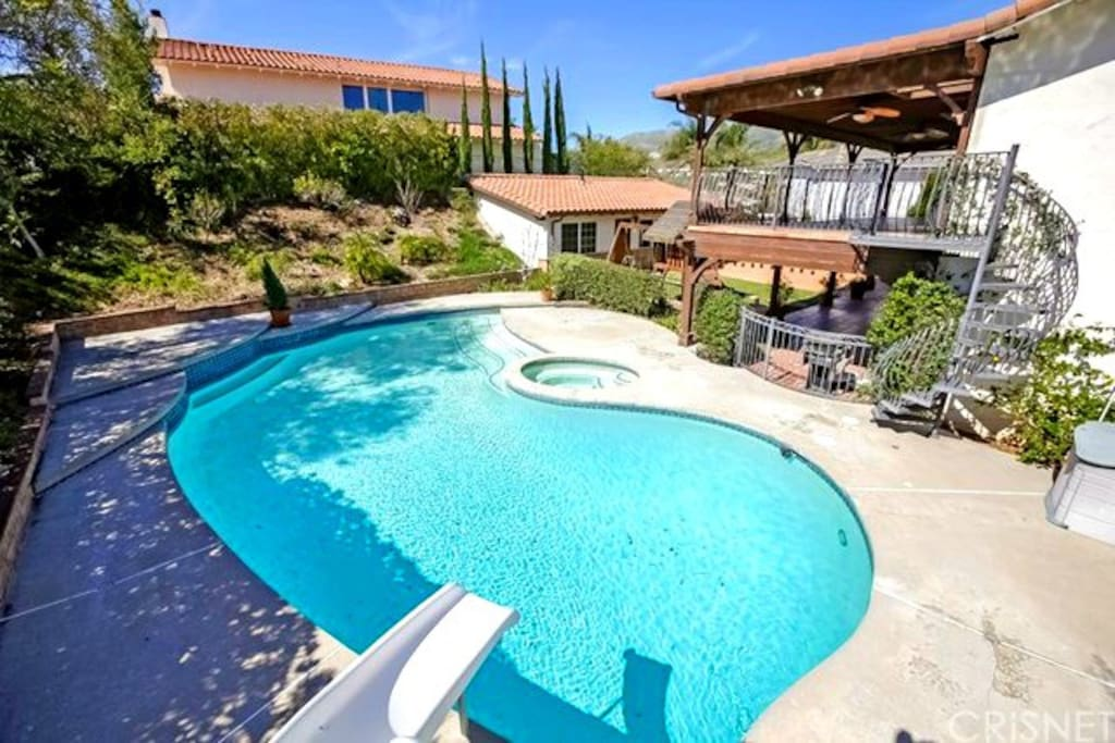 Huge family sized pool equipped with slide is a perfect day in activity.