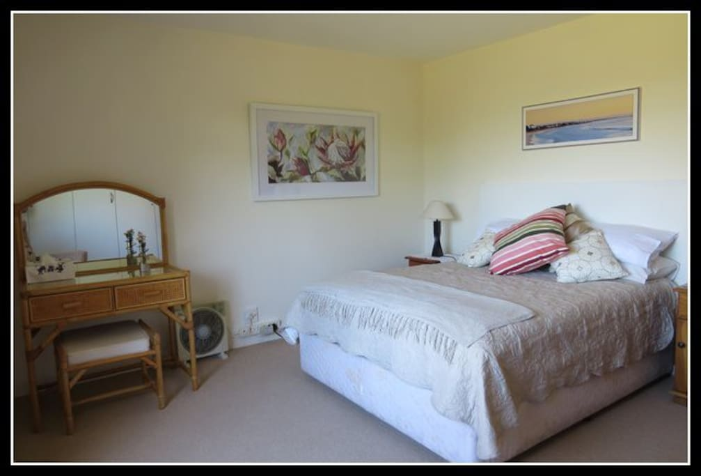 Large sunny bedroom with queen size bed.
