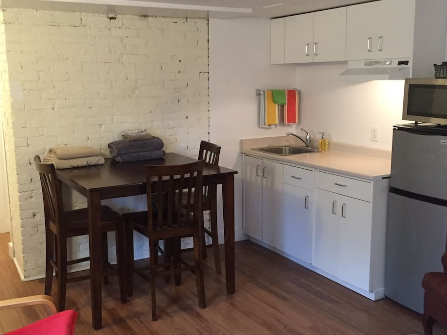 Fully stocked kitchenette: kettle, counter top plug in 2 stove burner, toaster oven, microwave, 3/4 size fridge; dishes; pots & pans; high table for eating or working.