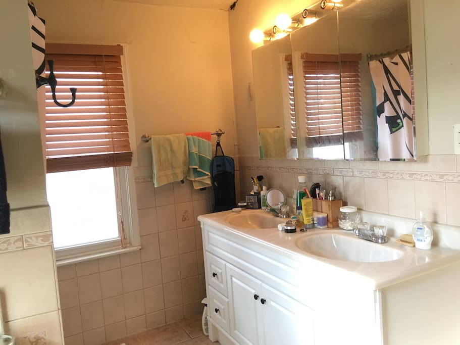 large bathroom with tub and double sink