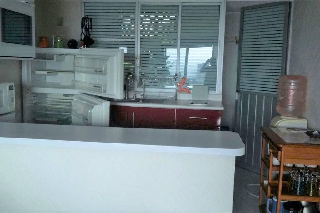 Cocina con refrigerador, estufa eléctrica, horno de microondas, en la parte de atrás zotehuela con lavadora y espacio para colgar ropa