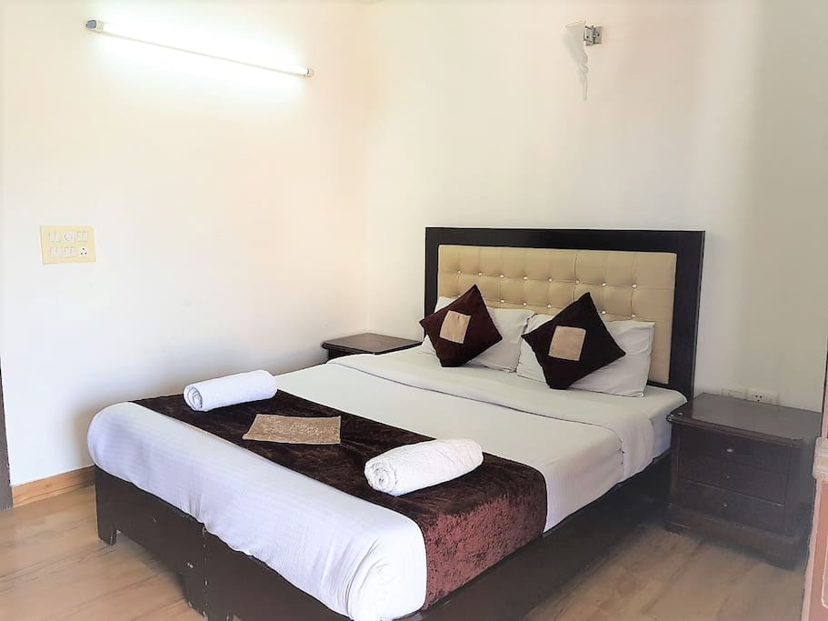 """Queen Bed with premium mattress and 32"""" Flat screen TV with Tata Sky HD."""