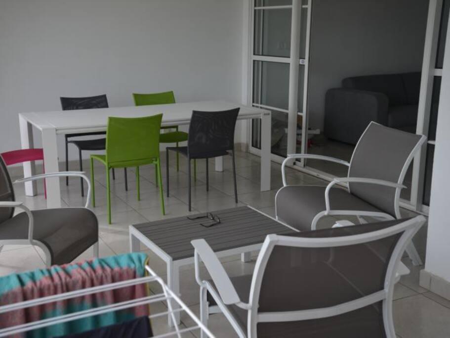 Terrasse équipée d'un salon d'extérieur et d'un table de S à M pour 8 personnes