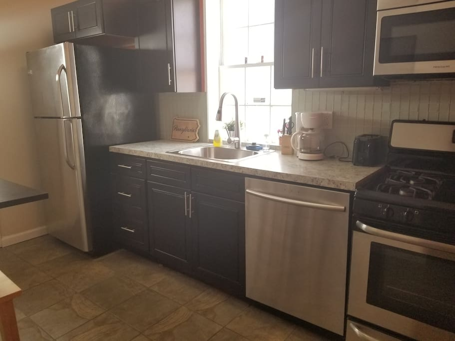 Kitchen view, new stainless steal fridge, dishwasher, sink, stove, and microwave.