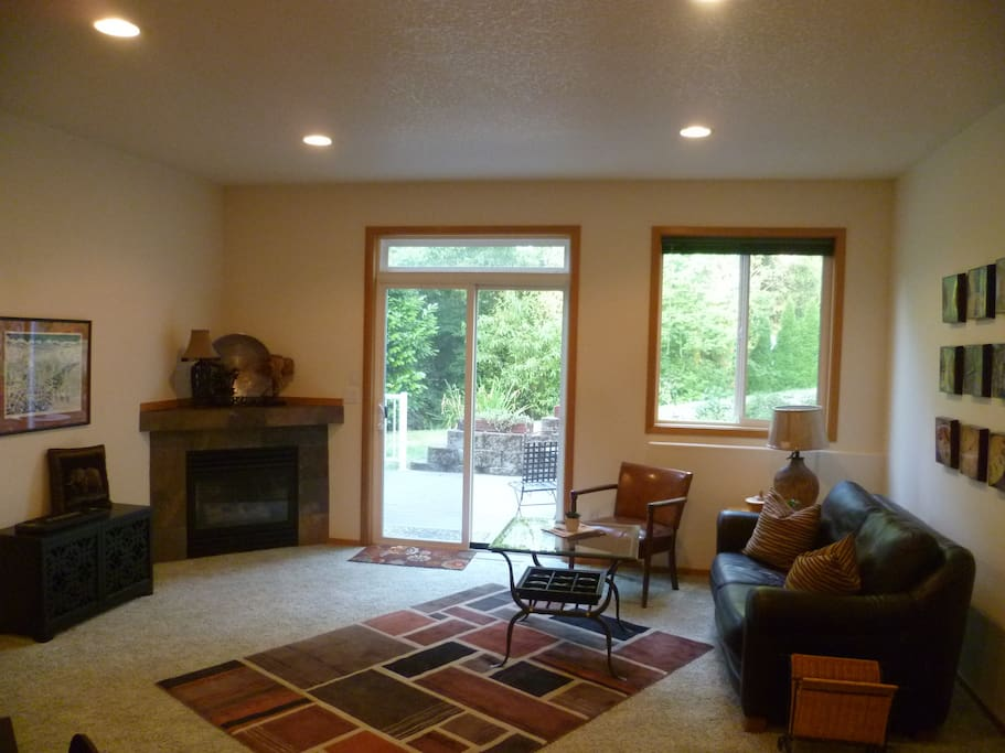 Relax in the living room with view of peaceful wooded outdoors and private patio!
