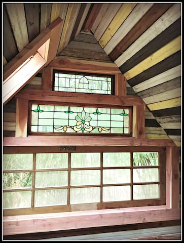 The southside gable as seen from the queen sized memory foam bed in in the sleeping loft.  Late 1800s stained glass and a French door on its side.  We also have skylights in the ceiling so you can see the dancing bamboo.