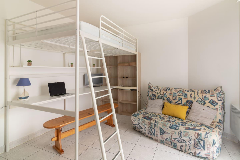 Salon avec lit mezzanine, coin bureau et canapé-lit