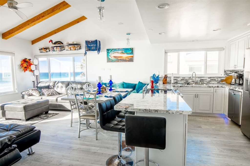 Living Area with large TV, bench seating, bar and custom kitchen