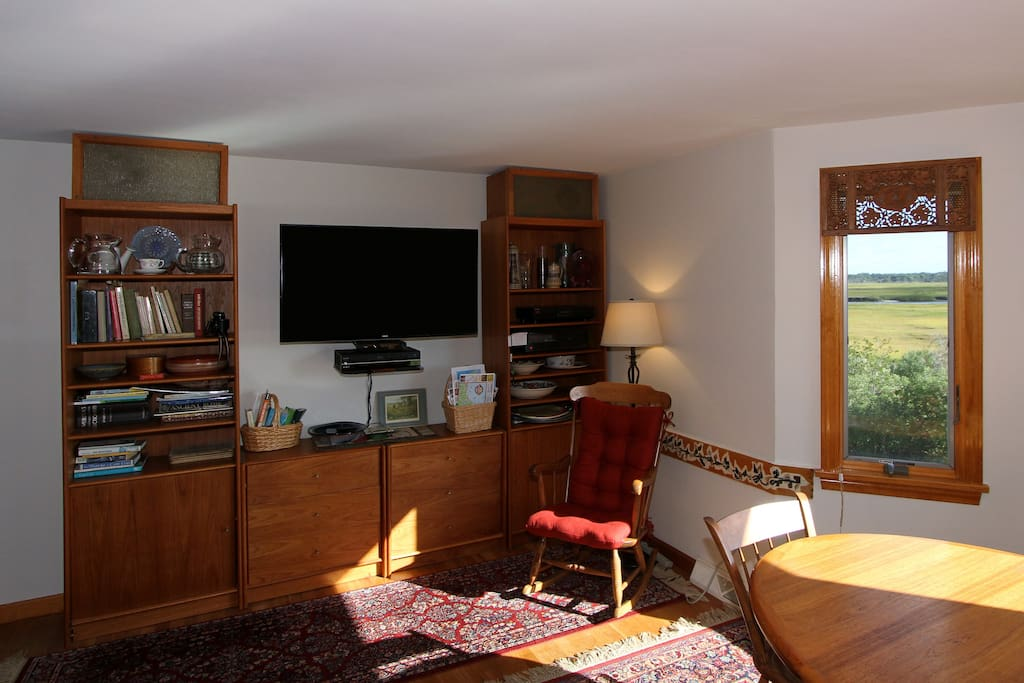 """There's a 48"""" flatscreen TV with cable  and beautiful oriental area rugs in the sunlit living room."""