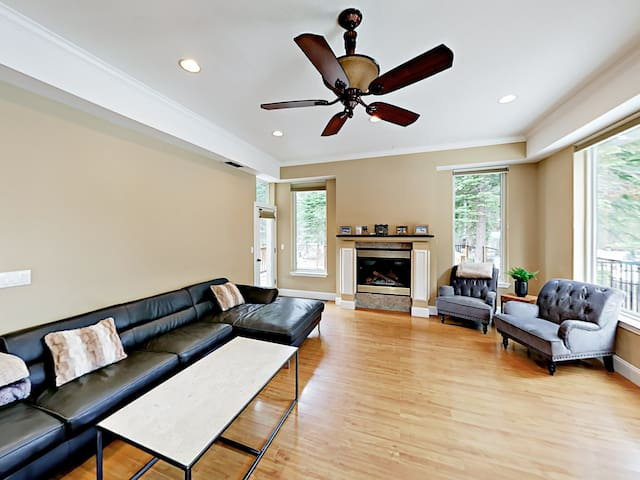 Picture windows line the open-concept living room. A gas fireplace adds warm ambience.