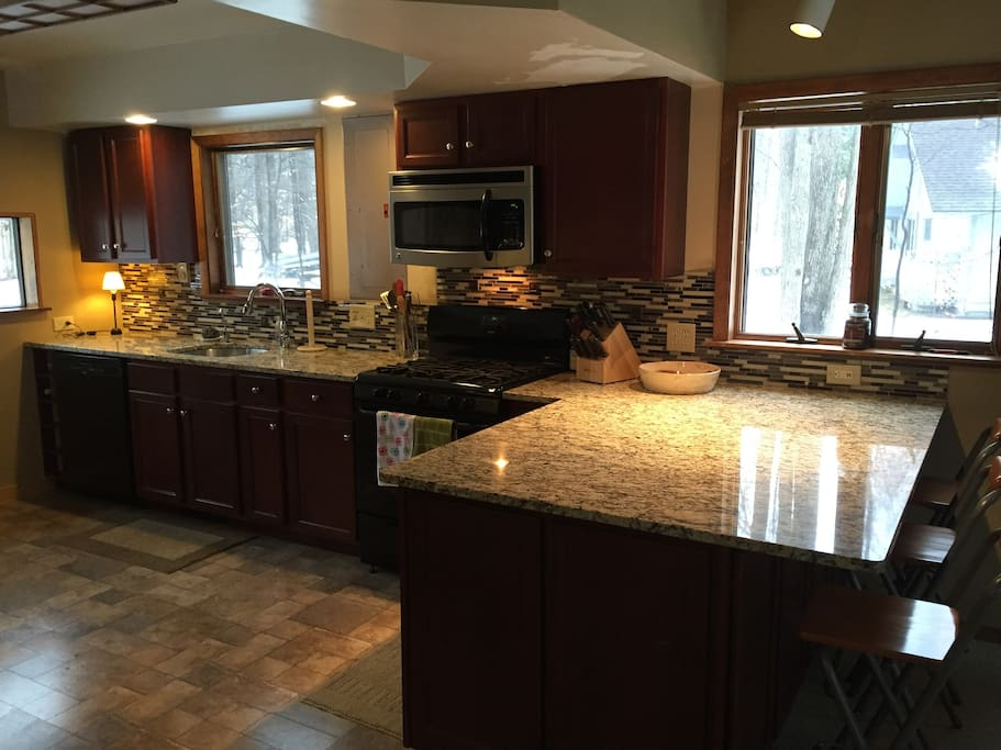 Kitchen with granite countertops, seating for three, Keurig machine, stackable washer and dryer with a door leading out to the back deck