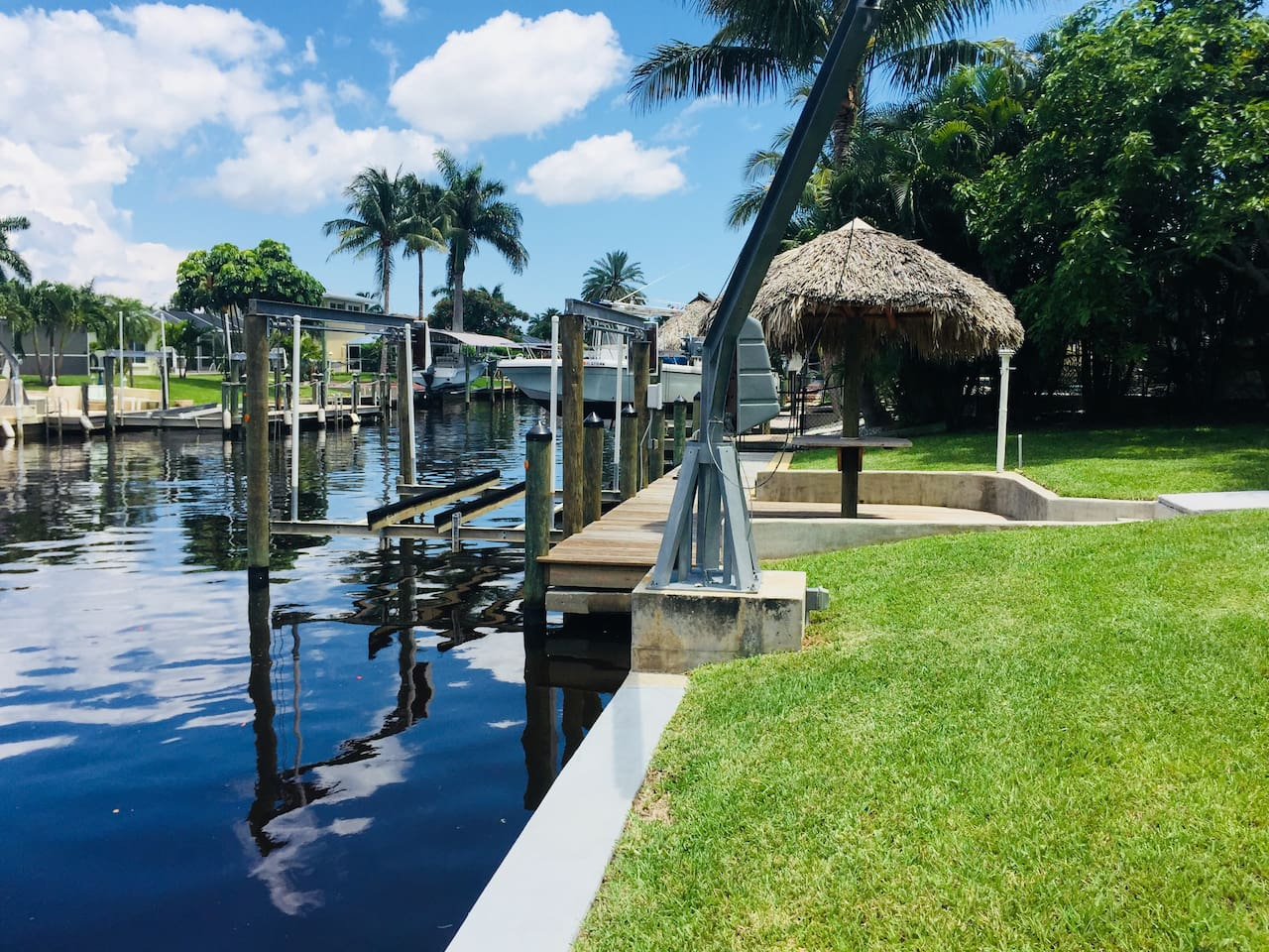 This is the other view that sold us on the house!  We love the back yard and water view!  Relax on the dock in one of our Adirondack chairs or at the tiki hut.  Keep your boat on our electric boat lift during your stay.