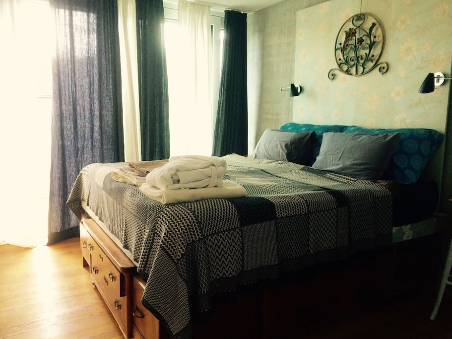 King Size Bed with 2 new matresses 90 x 200 middle soft, placed on comodes where we leave our belongings, while you live in our home. Height of the bed: 78cm. Small Private Balcony from the bedroom, big triple window with shades and courtains.