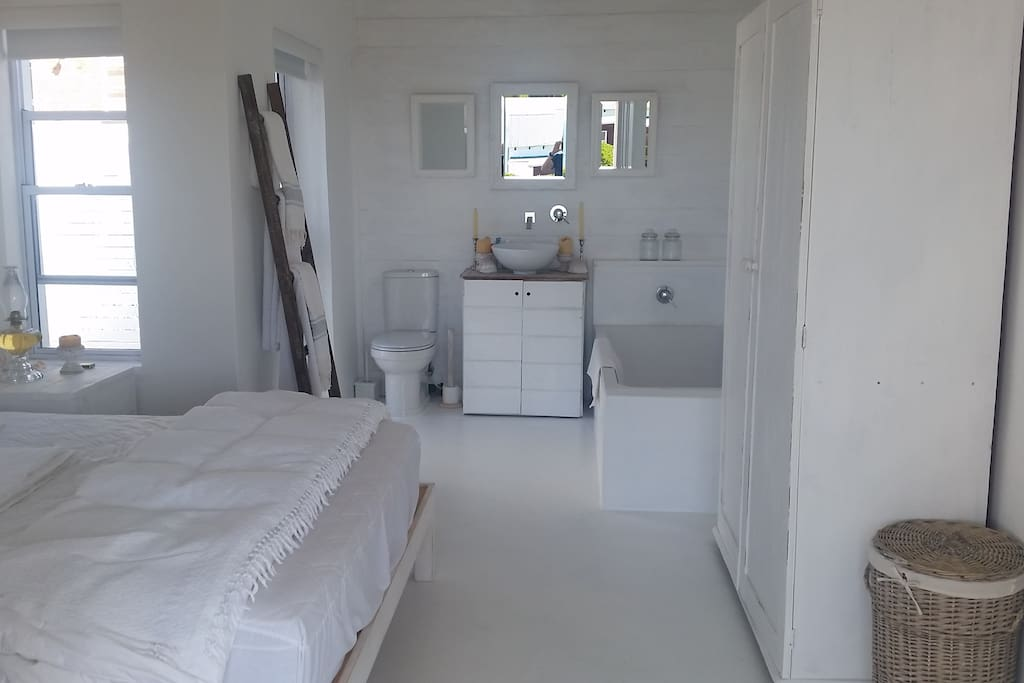 main double bedroom with bathroom with outside open shower. This bedroom also leads onto covered deck with view