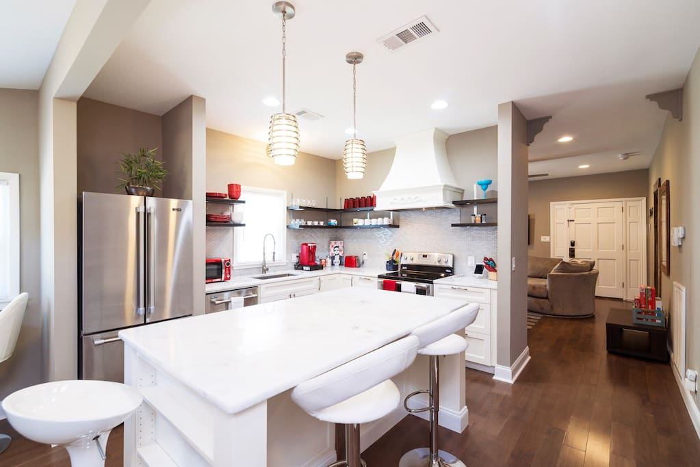 The modern kitchen is a showstopper with marble countertops and a full suite of stainless steel appliances.