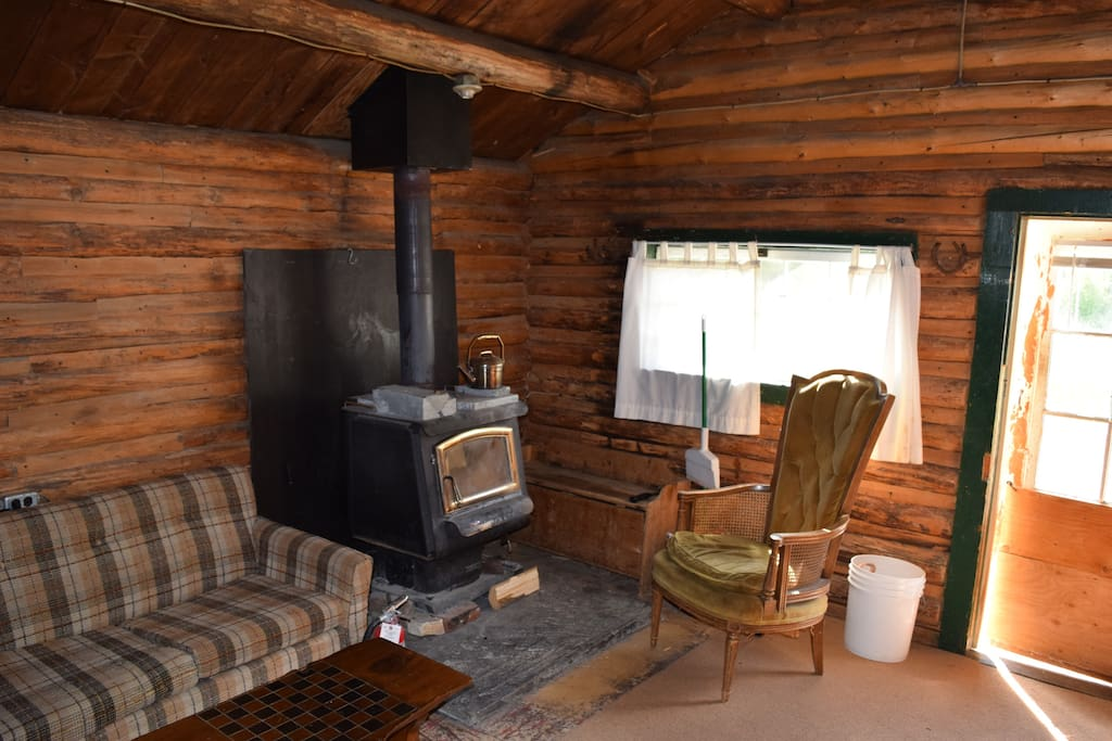 The seating area and woods stove in the cabin.