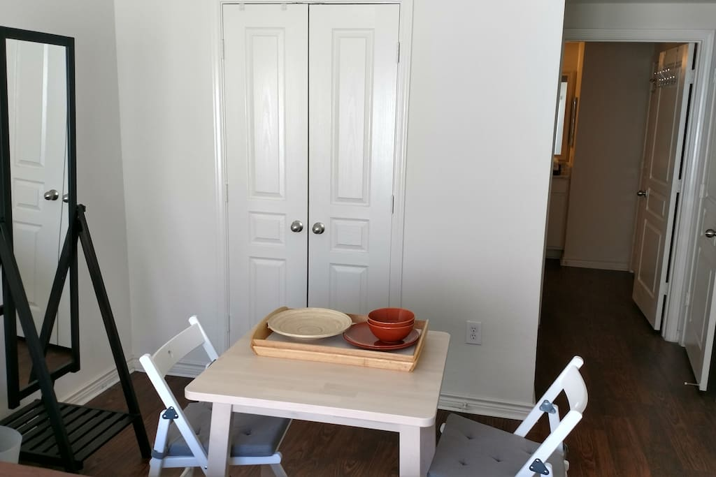 full walk in closet, mirror, and table in master
