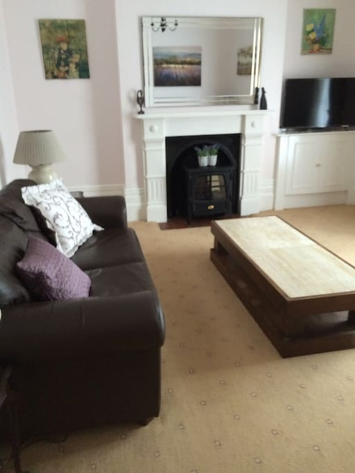 Comfy, airy and spacious sitting room with wide screen TV. French doors lead to pretty front garden.