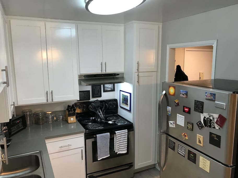 Kitchen with all the necessities, new stove, and countertop dishwasher.