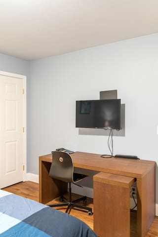 Desk with roll out extension. Surge protector for easy power access. Wall mounted television has HBO, Netflix, ad-free Hulu, and an antenna for over the air content.