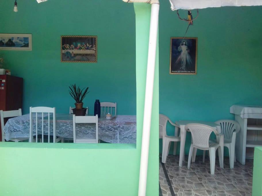 área com cozinha compartilhada, fogão, geladeira, e espaço para mesas e cadeiras