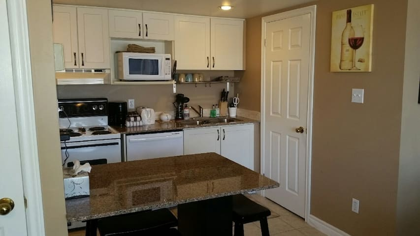 Kitchen with granite countertops & eating area with 4 bar stools. Stocked with dishes, cutlery, pots/pans, toaster, microwave, kettle,  basket-style drip coffee-maker & filters, fridge, stove, cloths, soap, dishwasher pucks, Brita water filter jug.