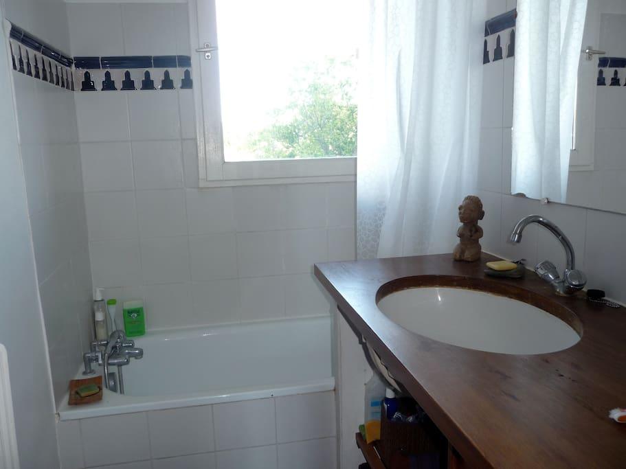 Salle de bains ajourée, vasque sur plan en bois, douche, machine à laver.
