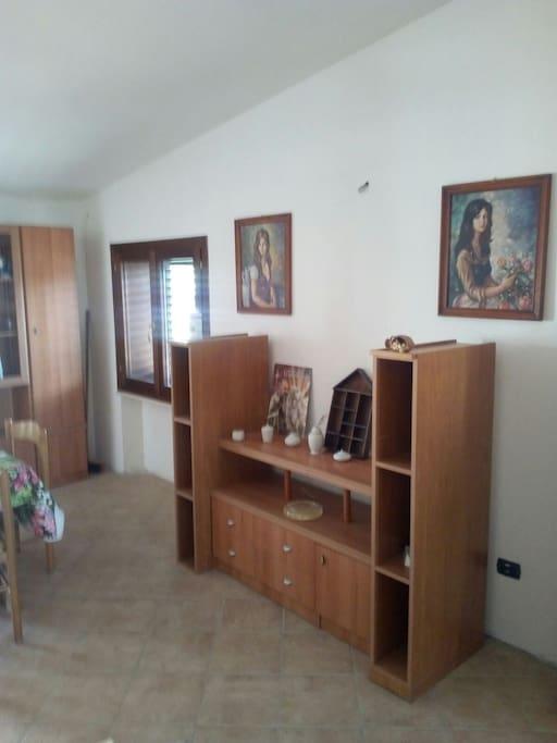 Sala e cucina con porta finestra che permette l'accesso ad un ampio terrazzo