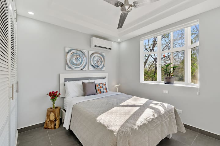 Guest bedroom with modern lighting,  dedicated air conditioner, full closet,  and bay window view of the trees