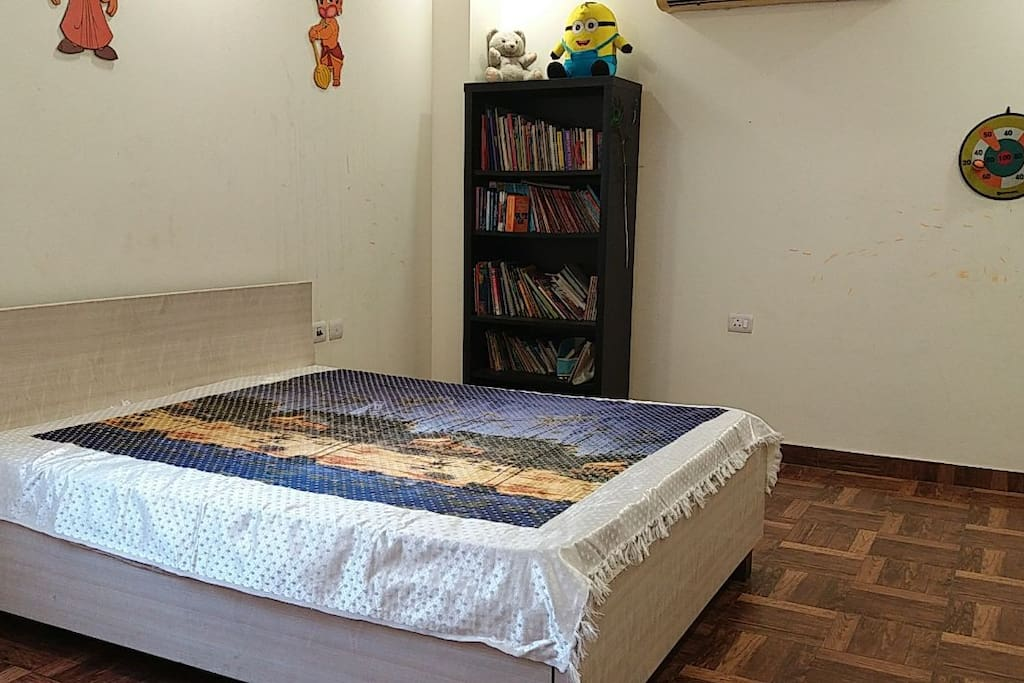 Your spacious bedroom with books on one side!