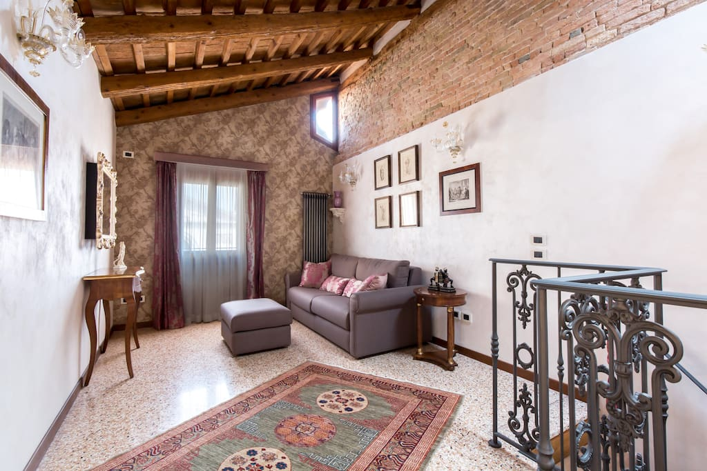 The spacious high-ceilinged living room offers a cosy atmosphere and remarkable view over Campo San Maurizio