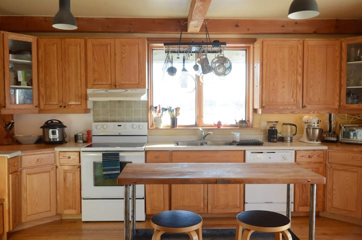 Kitchen with all the appliances and a great island, with four stools.