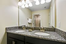 This shared family upstairs bathroom offers tiled floors, mirrored vanity unit with two sinks, toilet and walk-in shower.
