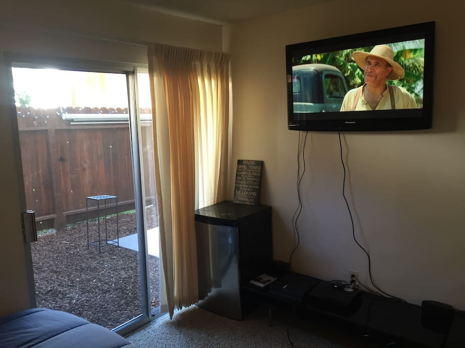 Room with patio entrance flat screen tv fridge PlayStation