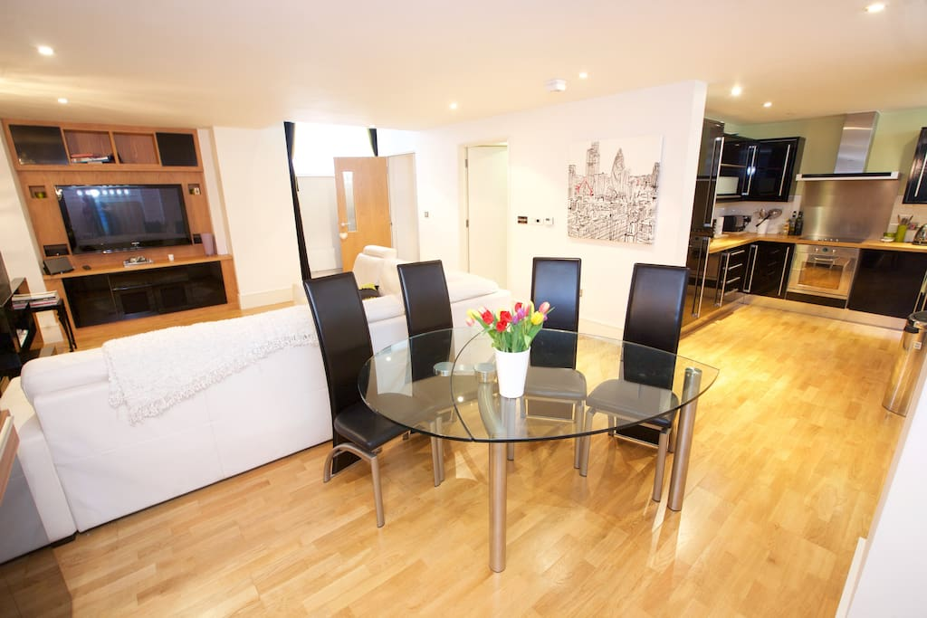 Here is the main reception room: a large sofa area to relax and watch TV, dining table that comfortably seats up to four, opening up into the kitchen