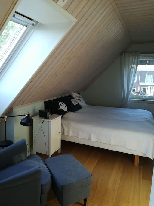 Eget låsbart sovrum med stor dubbelsäng, takfönster och en bekväm läsfåtölj