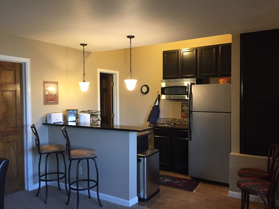 Kitchen with refridgerator, microwave/oven, and two burner stove top. Two bar stools, plus small kitchen table.